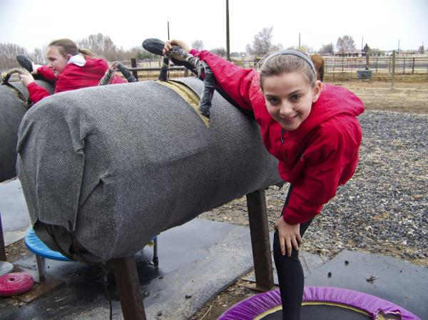 Jazmyn Wentland, 10, and another vaulter on her team warm up with stretches and practice on a barrel before they do their routines on horses in Moses Lake, Wash.