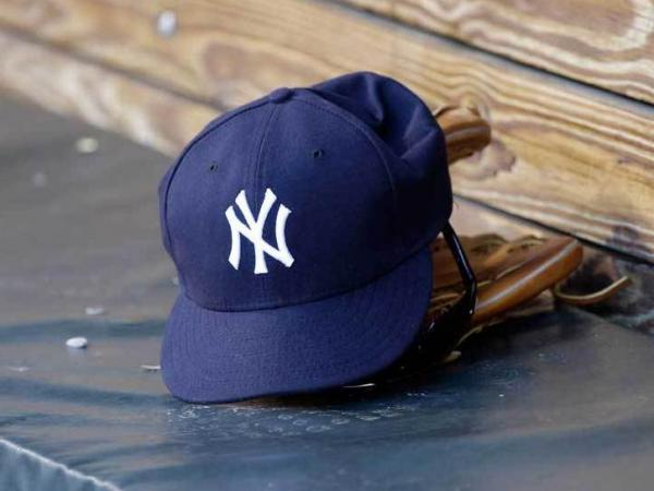 A New York Yankees hat and glove rest in the dugout before a game at Oriole Park at Camden Yards.