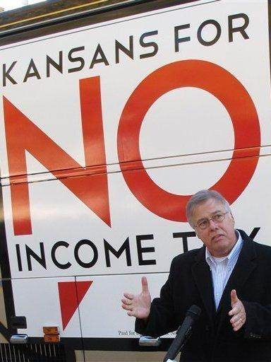 In Kansas, legislators are considering devoting extra funds to tax relief instead of hiring more state workers. Republican state Rep. Joe Patton of Topeka, shown in November, talks about proposals to eliminate the state's income tax.
