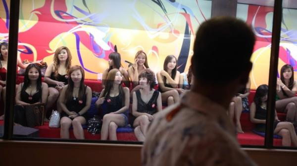 A man eyes some of the women working at the upscale Fish Tank brothel in Bangkok. The documentary <em>Whores' Glory </em>chronicles the experiences of sex workers in relatively clean establishments — and some living in de facto slavery.