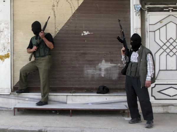 Syrian opposition fighters stand watch in a suburb of Damascus, Syria, on April 6. A cease-fire was declared several days later, but shooting has continued.