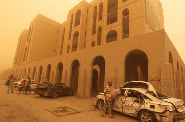 Iraqis inspect a car destroyed in a car bombing in Baghdad's Haifa Street, as dust creates a yellow haze across the city on Thursday.