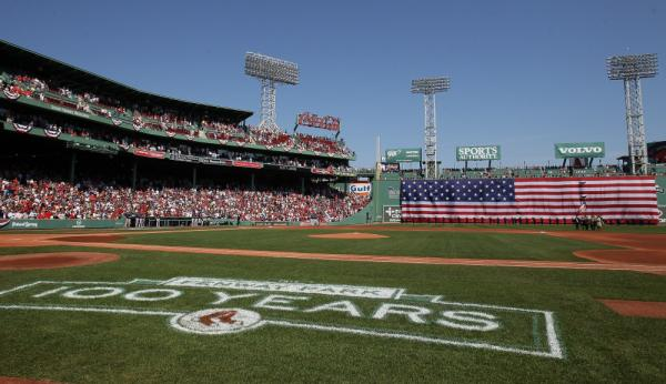 The flag covers the Green Monster as the national anthem is played before the game between the Boston Red Sox and the Tampa Bay Rays on April 16 at Fenway Park in Boston.