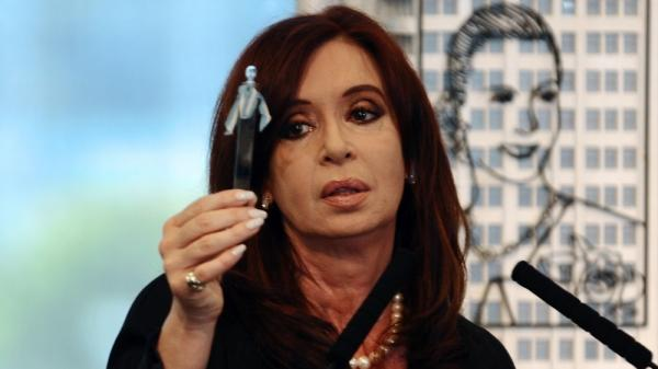 Argentine President Cristina Fernandez holds up a petroleum sample as she announces plans for her government to nationalize a giant oil company that is largely owned by a private Spanish company. Behind her is an image of the country's former first lady, Eva Peron.