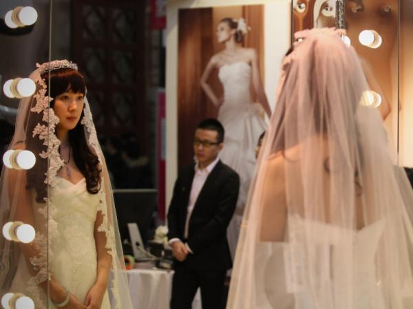 A Chinese woman tries on a wedding dress at the 2012 China Spring Wedding Expo at Beijing Exhibition Center on Feb. 17, 2012 in Beijing, China.