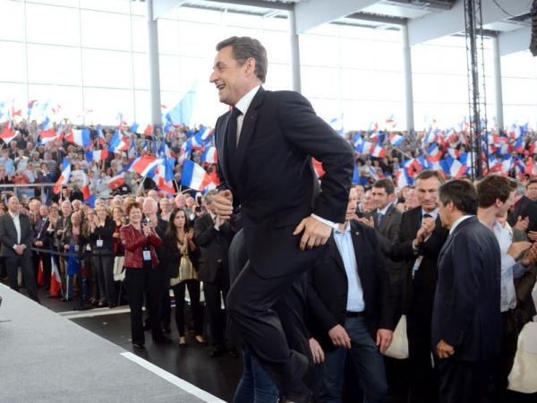 France's incumbent President Nicolas Sarkozy arrives on stage to deliver a speech during a campaign meeting in Cernay, eastern France, on April 25, 2012. Sarkozy will face his rival Socialist Party Francois Hollande in a final round on May 6, 2012.