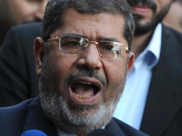 Mohammed Morsi, leader of the Freedom and Justice Party (FJP), speaks to the media outside a polling center in Qaliubia, 40 kilometers north of Cairo, during the third and final round of landmark parliamentary elections on Jan. 3, 2012.