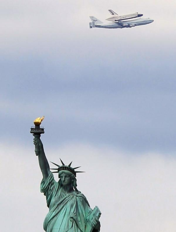 Riding atop a 747 shuttle carrier aircraft, the space shuttle Enterprise flew past the Statue of Liberty in New York Harbor today.