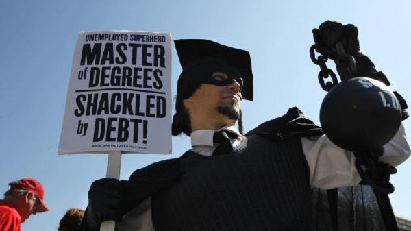 "Gan Golan of Los Angeles, dressed as the ""Master of Degrees,"" holds a ball and chain representing his college loan debt during Occupy D.C. activities in Washington. Average in-state tuition and fees at four-year public colleges rose an additional $631 this fall, or 8.3 percent, compared with a year ago."