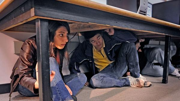 Academy of Art University students Lisa Allen (left) and Shaofu Zhang take part in the California ShakeOut — a statewide Drop, Cover and Hold earthquake drill in San Francisco on Thursday. University of California, Berkeley scientists are working on an earthquake early-warning system.