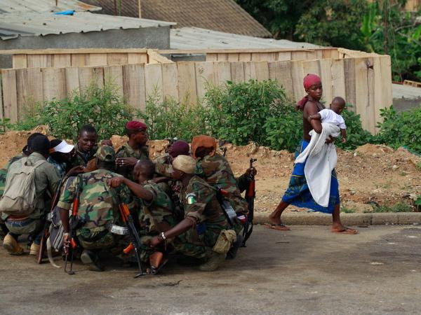 A local resident walks past forces soldiers loyal to Alassane  Ouattara as they share a morning meal.