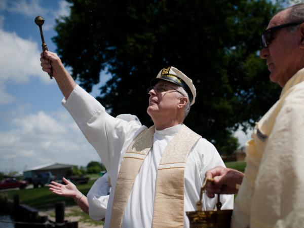 Monsignor Frederic Brunet blesses the boat the Maycie Brooke before climbing aboard the vessel to begin the boat blessing parade, in Chauvin, La.