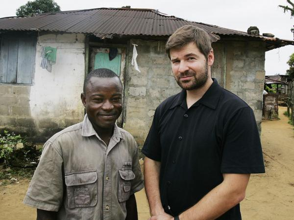 Photojournalist Chris Hondros poses with a a former Liberian government soldier, at his home in Monrovia, Liberia, in 2005. Hondros' picture of Duo jumping into the air in exultation during a battle with rebel forces in 2003 was distributed around the world. Hondros was killed April 20 in Misrata, Libya.