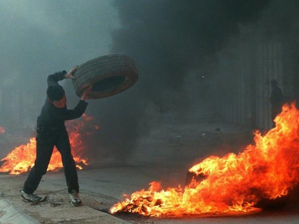 In the late 1990s, both Marinovich and Silva traveled to the Middle East to photograph the ongoing clashes in the region. Silva captured this image of a young Palestinian boy throwing a tire in the West Bank town of A-Ram in March 1997.