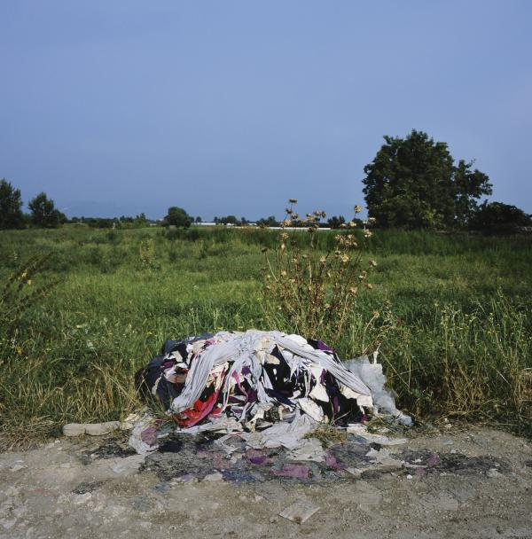 A pile of illegally disposed clothing scraps from a local tailoring company lies abandoned next to a farm near Marigliano, Italy. Piles of urban waste can be found throughout the provinces of Naples and Caserta.