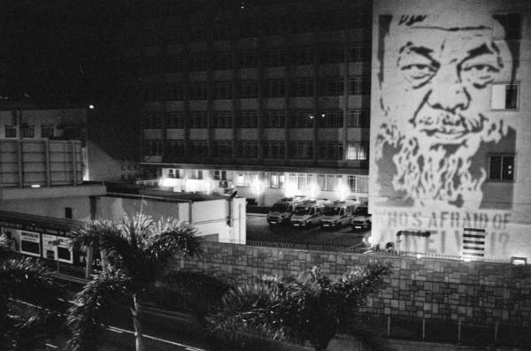 Flash graffiti of Ai Weiwei projected for a split second onto the Chinese People's Liberation Army barracks in Hong Kong. The PLA says this is a breach of the law.