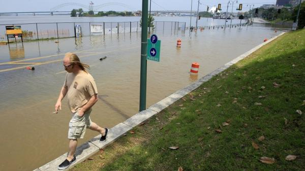 Casey Cummings walks along a wall as he takes a look at Mississippi River floodwaters Sunday on Riverside Drive in Memphis, Tenn.