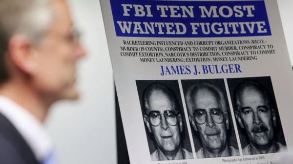"FBI special agent Richard Deslauriers speaks Monday during a news conference next to a poster featuring fugitive James ""Whitey"" Bulger at the FBI field office in Boston."