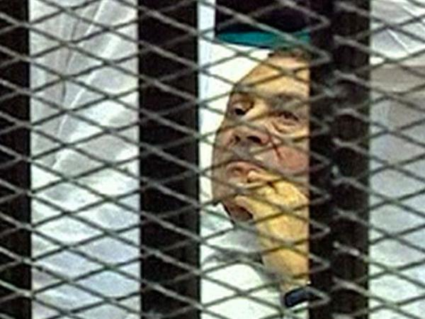 This video image taken from Egyptian State Television shows 83-year-old  Hosni Mubarak lying on a hospital bed inside a  cage of mesh and iron bars in a Cairo courtroom on Aug. 3.