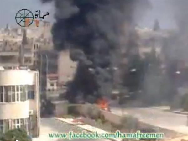 A screen grab of a YouTube video shows smoke rising in what appears to be a contested part of Hama, Syria.