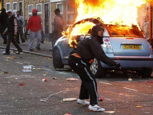 A rioter throws a rock at riot police in Clarence Road in Hackney, London, Monday. The wave of violence has spread to three other major British cities. The riots appeared to have little unifying cause — though some involved  claimed to oppose sharp government spending cuts, which will slash  welfare payments and cut tens of thousands of public sector jobs through  2015.