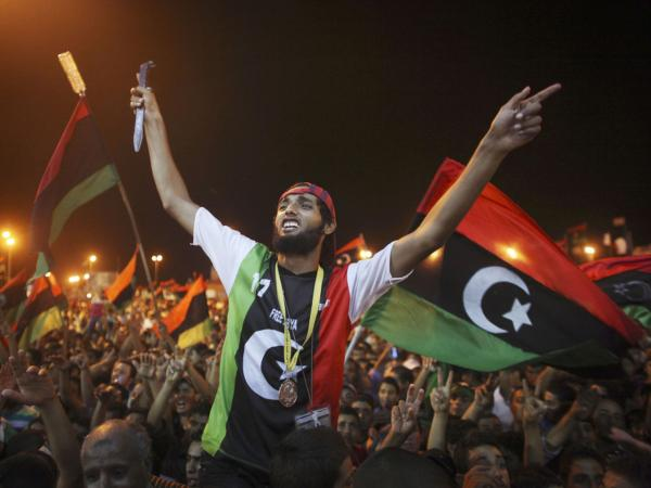 People celebrate the capture in Tripoli of Moammar Gadhafi's son and one-time heir apparent, Seif al-Islam, at the rebel-held town of Benghazi, Libya, early Monday. Libyan rebels raced into Tripoli in a lightning advance Sunday that met little resistance as Gadhafi's defenders melted away and his 42-year rule appeared to rapidly crumble.