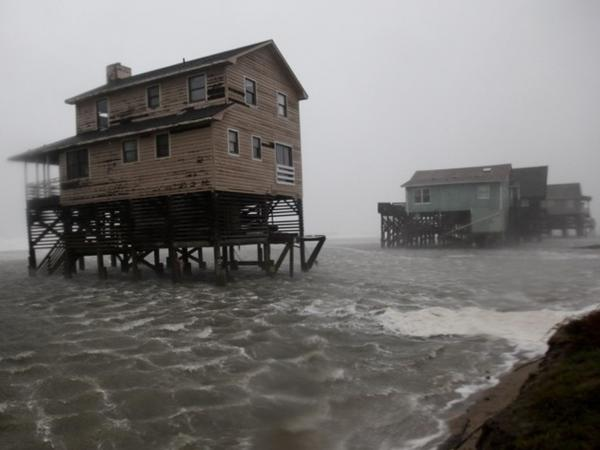 Abandoned beachfront houses are surrounded by rising water as the effects of Hurricane Irene are felt in Nags Head, N.C., on Saturday.