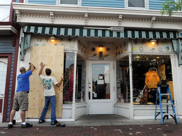 Chris Pittman (left) and Frank Eckel board up a storefront in Cape May, N.J., in anticipation of Hurricane Irene.