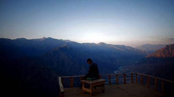 A member of the Afghan Security Guards looks over the Kunar River Valley from Observation Post Mustang in Kunar Province, northeastern Afghanistan.