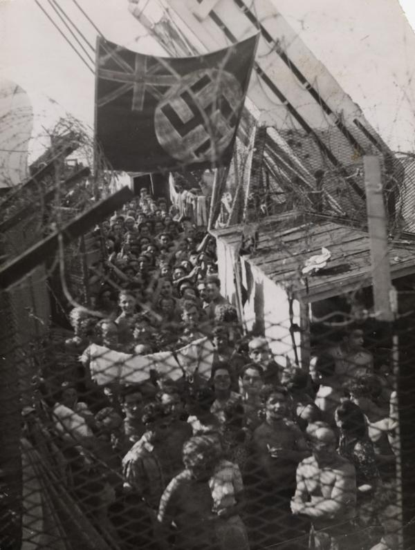 <p>Jewish refugees, having been forced off <em>Exodus 1947</em> in Haifa, Palestine, wait aboard the British prison ship <em>Runnymede Park</em> on Aug. 22, 1947. In protest, the prisoners painted a swastika on top of the Union Jack. </p>
