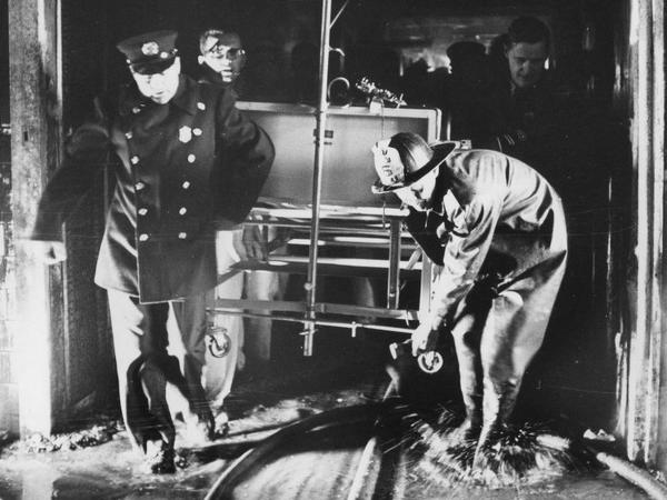 Rescue workers carry a hospital bed through a flooded corridor at Hartford Hospital in 1961.