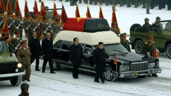 This photo provided by Korean Central News Agency (KCNA) shows Kim Jong Un, center, with his hand on the limousine bearing his father Kim Jong Il's body during the funeral procession in Pyongyang.