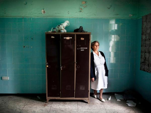 Nurse Stella Trivizaki stands in an abandoned locker room at Asklypeio Public Hospital in Athens, Greece.