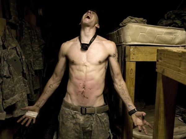 "Specialist Tad Donoho screams with pain after being administered a ""pink belly"" for his birthday: Each member of the platoon struck his stomach until it bruised. July 2008."