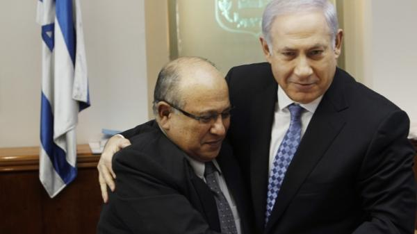 Israeli Prime Minister Benjamin Netanyahu embraces Meir Dagan, the then-outgoing chief of the Mossad intelligence agency, in January 2011. Dagan is among former security chiefs who have recently criticized Netanyahu, saying he has exaggerated the urgency of the threat posed by Iran's nuclear program.