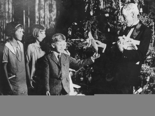 John D. Rockefeller handing out Christmas presents to a group of children.