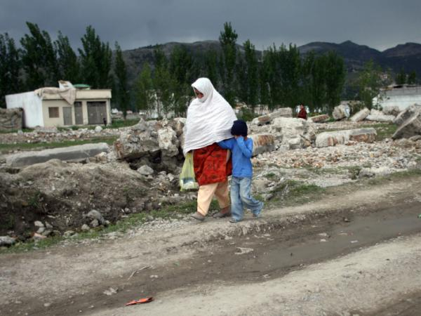 Pakistanis walk past the rubble of bin Laden's demolished compound this week.