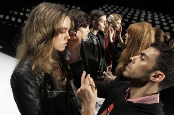 In this Feb. 15, 2012, file photo, models have their make-up finalized under runway light before the J. Mendel Fall 2012 collection is modeled during Fashion Week, in New York.