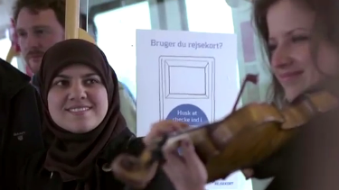 A woman listens to a violinist on the Copenhagen Metro.