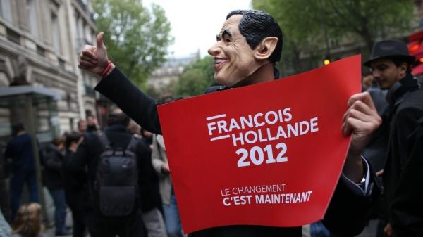 A supporter of French President-elect Francois Hollande wears a mask of outgoing President Nicolas Sarkozy.