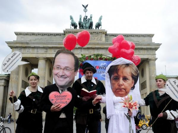 Activists wear masks featuring German chancellor Angela Merkel and incoming French socialist president Francois Hollande as they perform a fake marriage in front of the Brandenburg Gate in Berlin, on May 7, 2012.