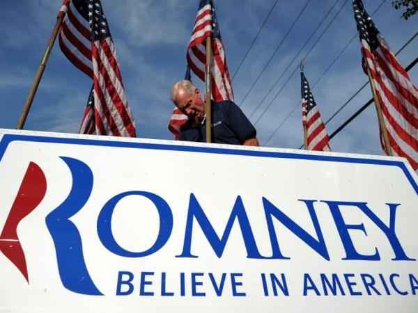 A man adjusts a campaign poster of Republican presidential candidate Mitt Romney in Chantilly, Virginia, on May 2, 2012.