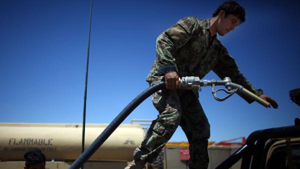 U.S. troops are training Afghan soldiers to take more responsibility in the war against the Taliban. But the Afghans still depend heavily on the Americans. Here, an Afghan solider fills up gas cans with diesel fuel from a U.S. Army tanker in southern Afghanistan.