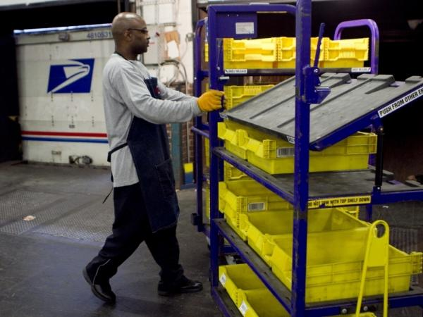 An employee loads flat trays onto a truck at the U.S. Postal Service processing and distribution center in Merrifield, Va. The USPS, which is projecting a $14.1 billion loss this fiscal year, is discussing restructuring options with potential advisers.