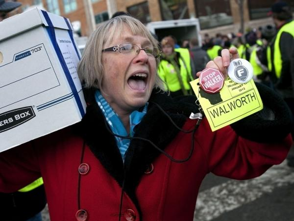 In this photo from January 17, 2012, a volunteer holds up recall badges as she carries one of the boxes containing signatures to recall Gov. Scott Walker into the Government Accountability Offices in Madison, Wisconsin. Over one-million signatures were collected in 60-days for a petition to recall Wisconsin Governor Scott Walker. 540,000 were required by law.
