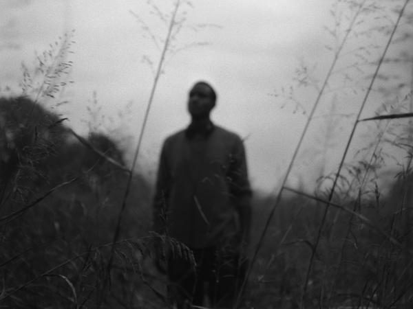 A young man stands alone in a field near his home in Mound Bayou, Miss., Nov. 2011.