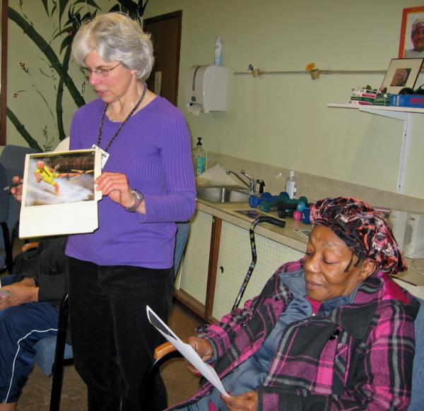 "Linda White (left) leads a session based on a program called <a href=""TimeSlips.org"">TimeSlips</a> at a Seattle senior center. The idea is to show photos to people with memory loss to help them make up a story."