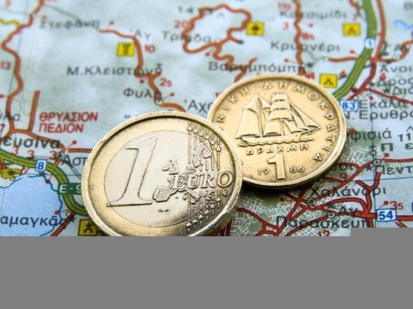 A euro coin and an old Greek drachma rest on a map of Greece. Some observers have predicted a Greek exit from the eurozone.