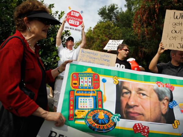 Protesters are seen behind a banner with a picture of JPMorgan Chairman and CEO Jamie Dimon outside a shareholders meeting Tuesday in Tampa, Fla.