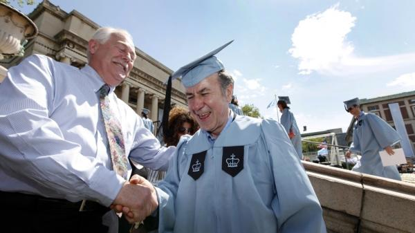 Columbia University janitor Gac Filipaj shakes hands with his boss, Donald Schlosser, the assistant vice president of facility operations.